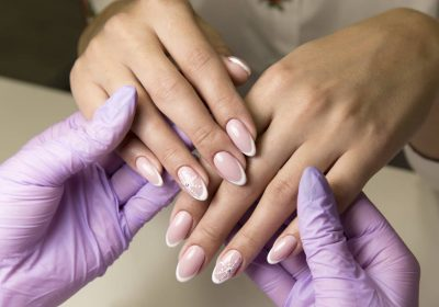 A beauty salon does a manicure to a rich client with black hair.
